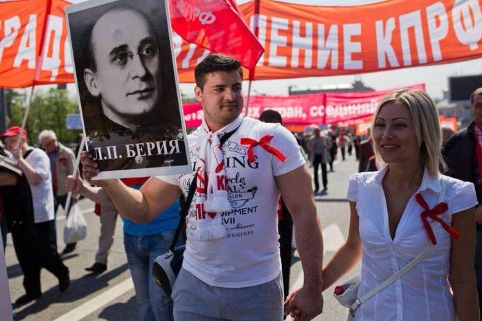 A young man carrying the picture of Lavrentiy Beria; a man responsible for Genocide, Moscow, 1st of May 2014