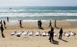 548x331_rescue_workers_stand_next_to_bodies_of_migrants_who_drowned_lie_on_the_beach_in_the_sicilian_village_of_sampieri