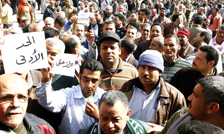 Mahalla textile workers carry signs that demands the minimum wage